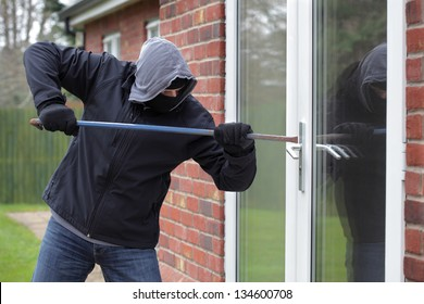 Burglar breaking into a house window with a crowbar