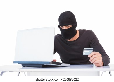 Burglar doing online shopping with laptop and credit card on white background