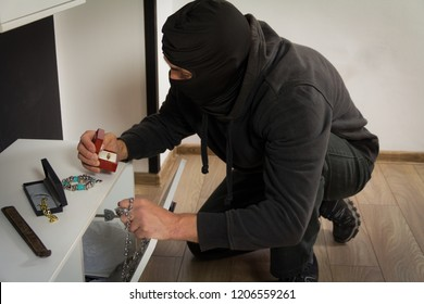 The burglar finds jewelry during theft. He finds a ring in the cabinet