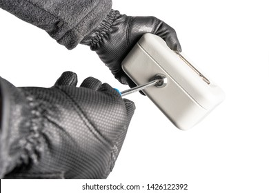 A burglar with gloves tries to break a petty cash