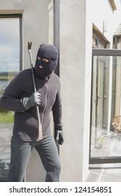 Burglar hiding behind wall with crow bar in back garden