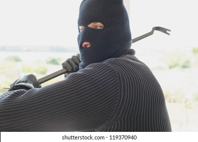 Burglar holding a crowbar and winding up while being in a house