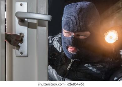 Burglar Holding Flashlight While Trying To Break Window Lock