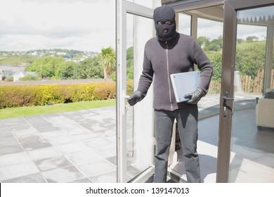 Burglar holding laptop and leaving home