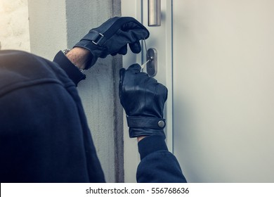 burglar holding Lock-picker to open a housedoor