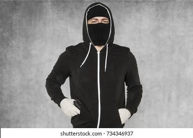 The burglar holds the gun in his pocket