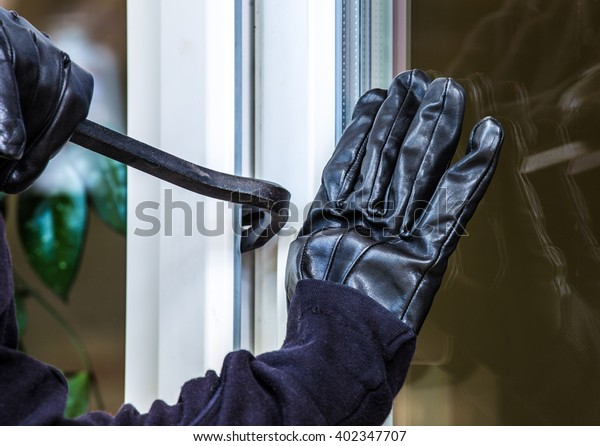 a burglar levers on a window