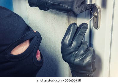 Burglar with lock picking tools breaking and entering into a house