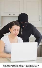 Burglar looking at the laptop behind  woman in kitchen