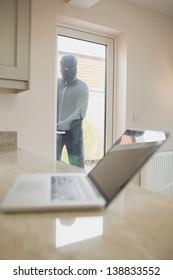 Burglar looking at laptop through the window of kitchen