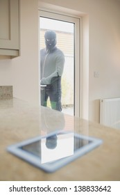 Burglar looking at tablet pc on kitchen counter through kitchen door