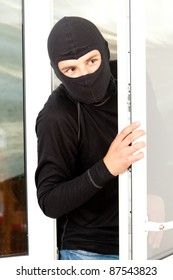 burglar  in mask and balaclava breaking into a house through window