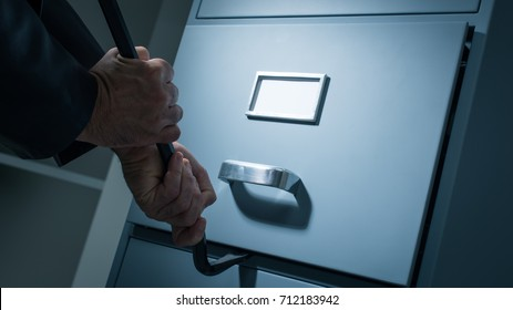 Burglar opening a drawer in the office at night using a crowbar, he is stealing confidential data and information, data theft and security concept