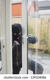 Burglar opening the terrace door with cro bar