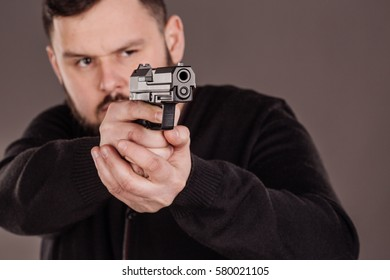 Burglar or robber aiming with pistol. dangerous and criminal situation