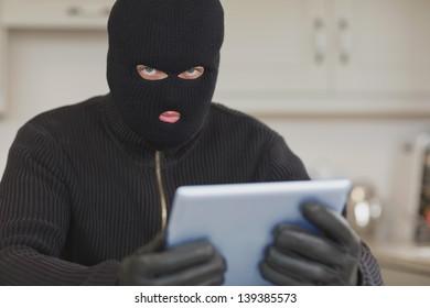 Burglar stealing the tablet pc in kitchen