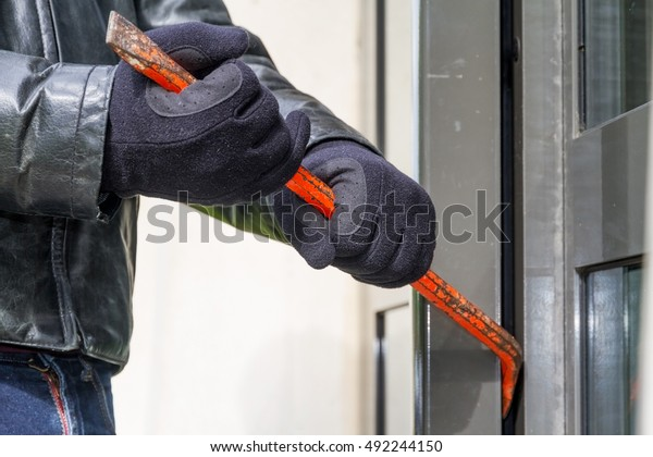 Burglar versucht in ein Haus mit einer Brechstange einzubrechen