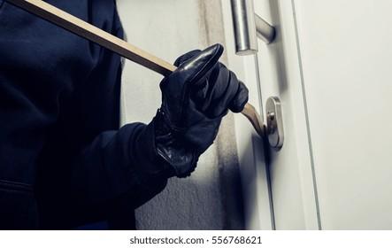 burglar using crowbar to break a home door at night