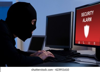 Burglar Wearing A Balaclava Breaking Security Alarm On Computer In Office