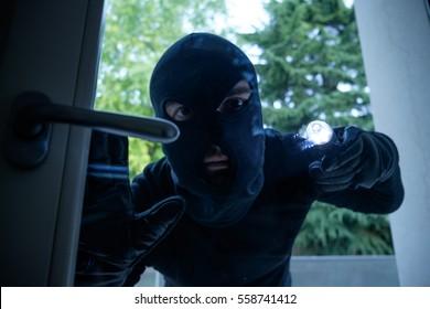 Burglar wearing a balaclava looking through the house window