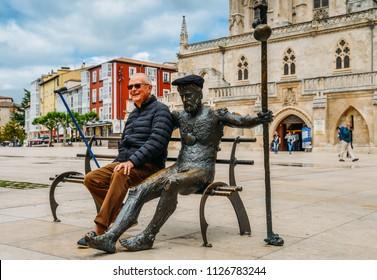 Burgos, Spain - June 13, 2018: Elderly man poses next to a tired pilgrim statue at Plaza Rey San Fernando in Burgos, Spain - Camino de Santiago reference