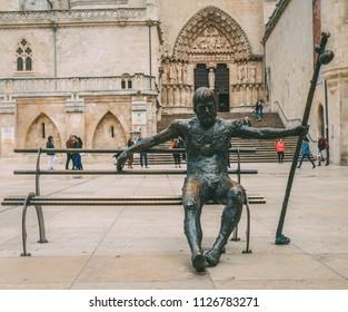 Burgos, Spain - June 13, 2018: Tired pilgrim statue at Plaza Rey San Fernando in Burgos, Spain. Camino de Santiago Way of St. James reference
