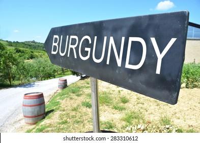 BURGUNDY arrow and wine barrels along rural road