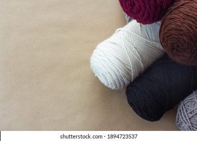 burgundy and brown yarn piled onto of white black and gray yarn