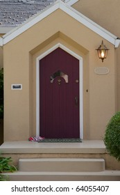 Burgundy door with unusual window on a white trimmed beige house with a lamp