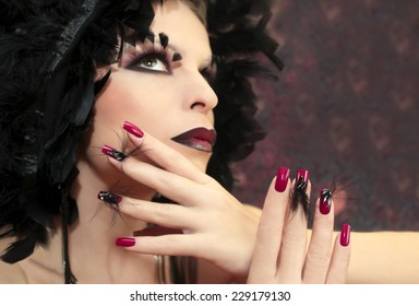 Burgundy manicure with feathers on the woman with the accessory on the head of feathers.