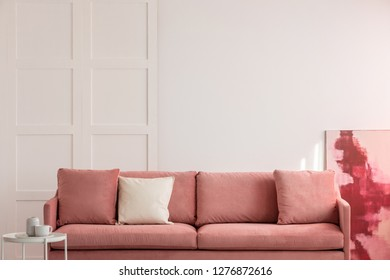 Burgundy and pastel pink abstract painting in white living room interior with velvet sofa with pillows