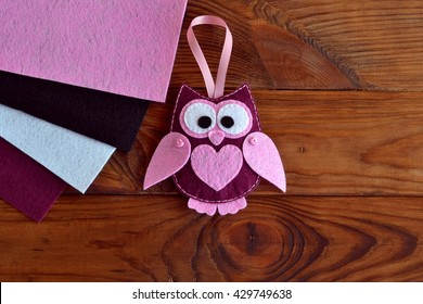 Burgundy and pink felt owl toy. Owl ornament. Stuffed owl sewing pattern. Felt bird plush softie. Keychain rearview mirror. Decoration mobile attachment. Home decor idea. Felt pieces.Wooden background