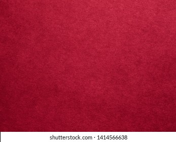 Burgundy red felt texture abstract art background. Colored fabric fibers surface. Empty space.