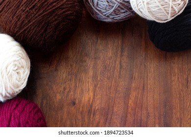 burgundy, white, gray, black, brown yarn balls on a wooden table
