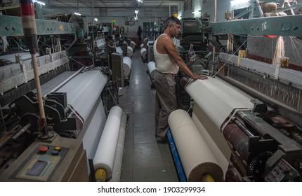 BURHANPUR, MADHYA PRADESH, INDIA 05 JAN 2021:A textile Loom factory worker work at Chinese Loom Machine in BURHANPUR, MADHYA PRADESH, INDIA 05 JAN 2021