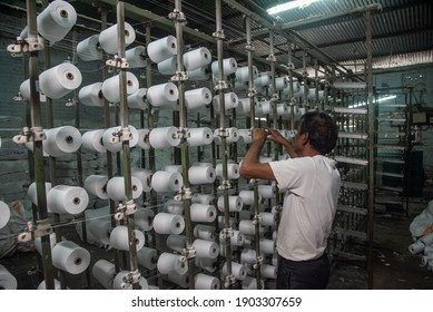 BURHANPUR, MADHYA PRADESH, INDIA 05 JAN 2021:A Loom factory worker work on Cotton Thread Bobins on a copwinder weft assembly line loom in.BURHANPUR, MADHYA PRADESH, INDIA