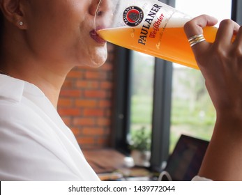 Buri Ram, Thailand - 07Apr, 2019 : Asian woman holding a glass of Paulaner Beer and drinking.