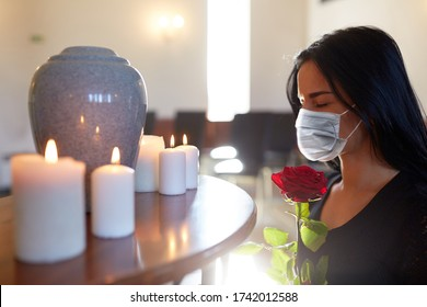 burial, people and mourning concept - sad woman wearing face protective medical mask for protection from virus disease with red rose and cinerary urn at funeral in church