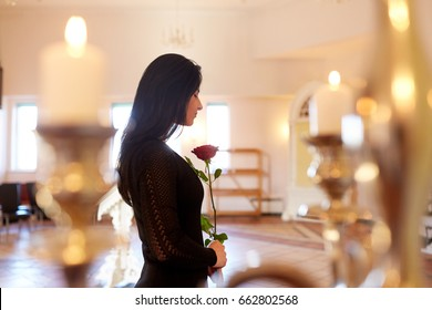burial, people and mourning concept - sad woman with red rose at funeral in church