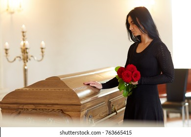 burial, people and mourning concept - unhappy woman with red rose and coffin at funeral in church