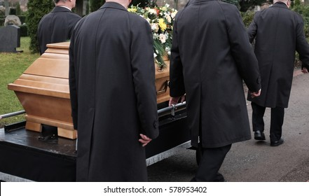 A burial process with a coffin to the grave