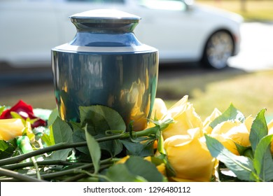 Burial urn with yellow roses, in a bright funeral scene, with a white hearse in the background and space for text on the right