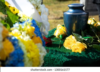 Burial urn with yellow roses in a funeral scene, with a floral wreath in the foreground, and space for text on the left