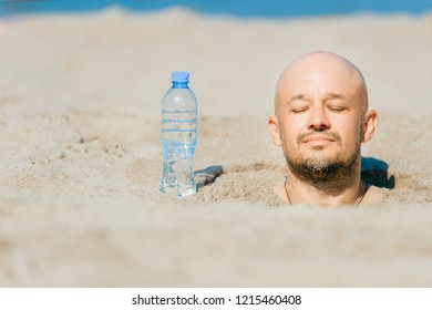 Buried till head bald man.  Suffering of thirsty male in desert. Young funny boy covered with sand on beach with bottle of water standing near. Slowly dying from dehydration male.  Summer sunstroke