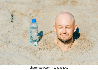 Buried till head bald man.  Suffering of thirsty male in desert. Young funny boy covered with sand on beach with bottle of water standing near. Slowly dying from dehidration male.  Summer sunstroke