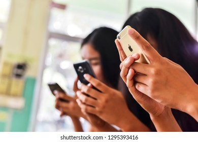 BURIRAM,THAILAND AUGUST 26,2017 : Unidentified three young people using Apple iPhone and Somsung together.In selective focus.Close-up. Technology gadget and phone addiction concept.