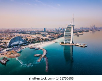 Burj Al Arab luxury hotel and Dubai marina skyline in the background at sunrise