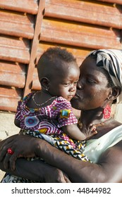 BURKINA FASO - AUGUST 9: mother kissing her daughter, women of ethnic Bissa lovingly of his children, August 9, 2009 in Country Bissa, Burkina Faso