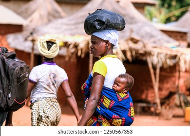Burkina Faso, Ouagadougou - August 22, 2018: African Woman with the Infant on the Back in the Traditional Clother