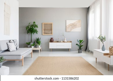 Burlap artwork on grey wall above white cupboard in bright living room interior with sofa and carpet. Real photo
